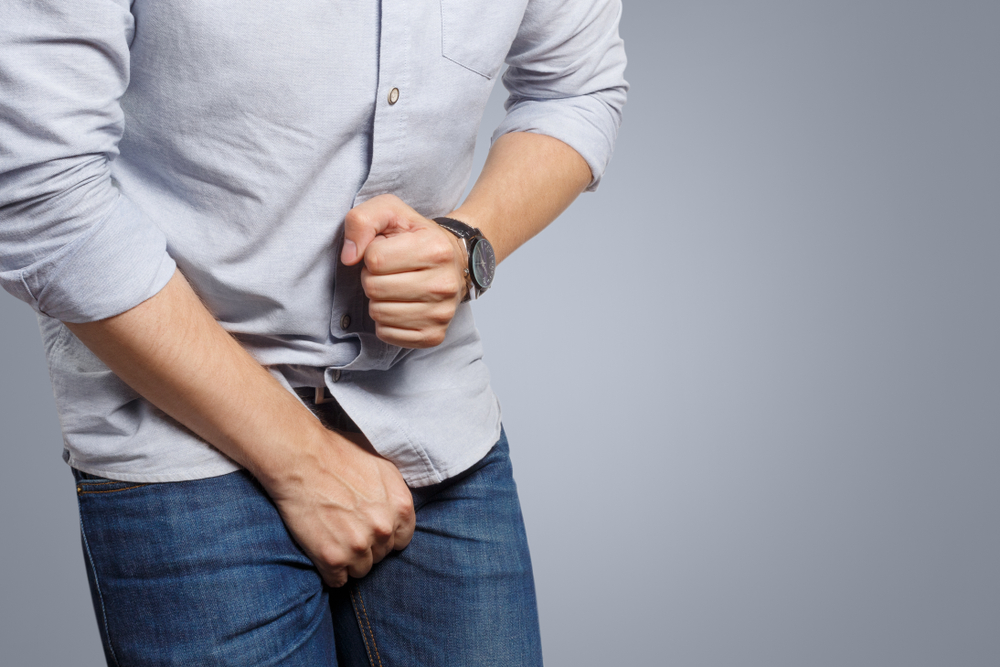 man clutching painful junk