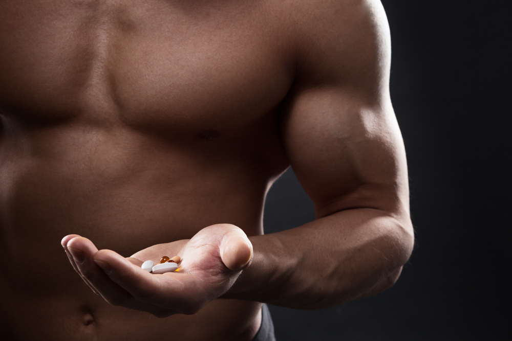 shirtless man holding supplements