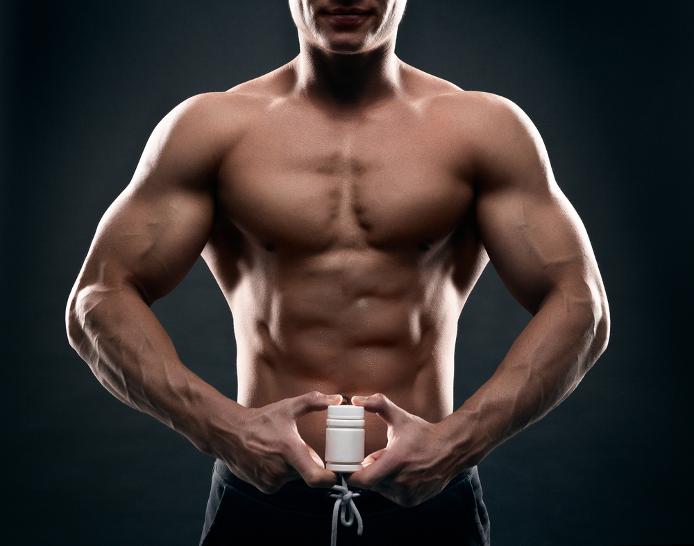 testosterone pumped man holding supplement bottle