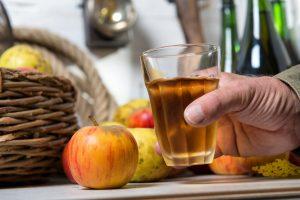 man holds glass of apple cider
