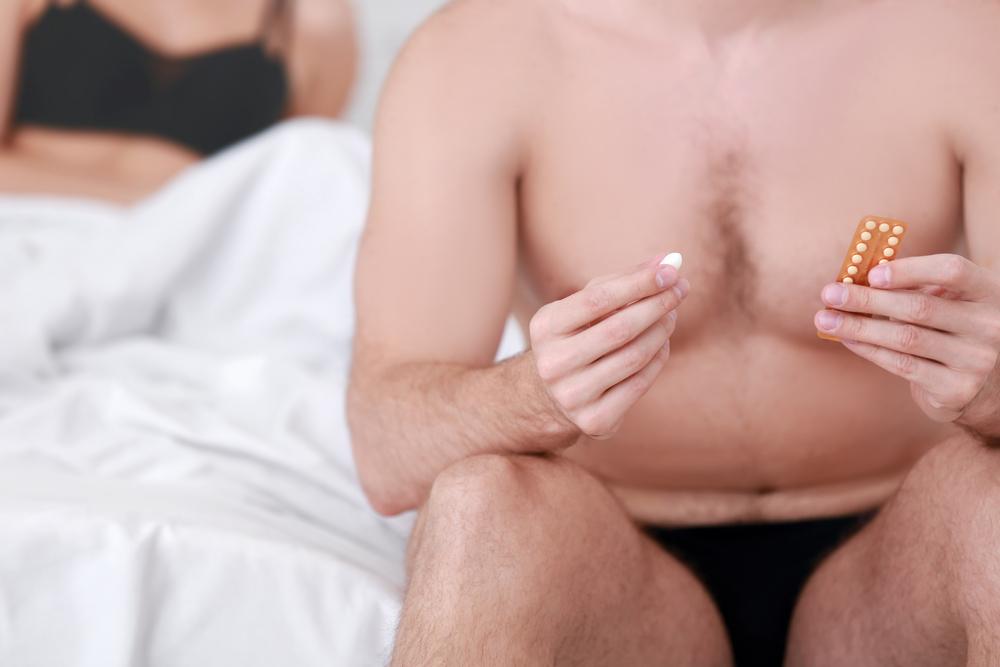man holding pill before sex