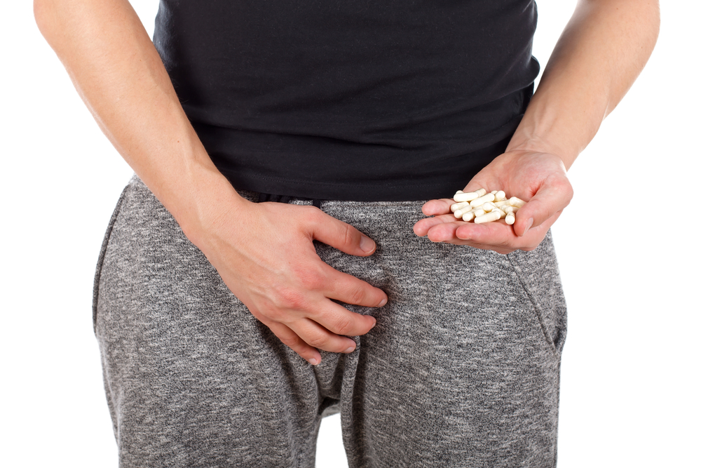 man holds crotch and some supplements