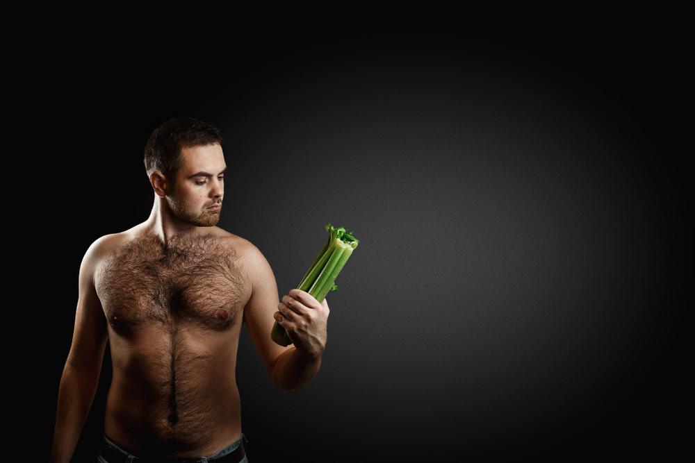 shirtless hairy man holding celery