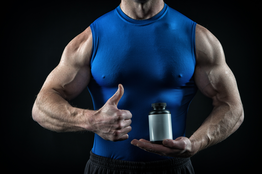 ripped guy holding supplement bottle