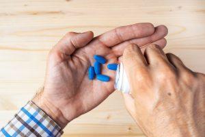 man taking blue pills