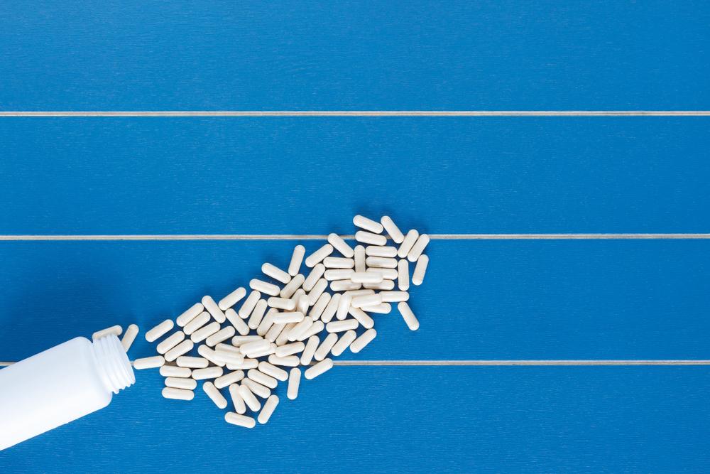spilled white pills on blue background