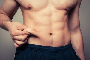 man pinching belly fat