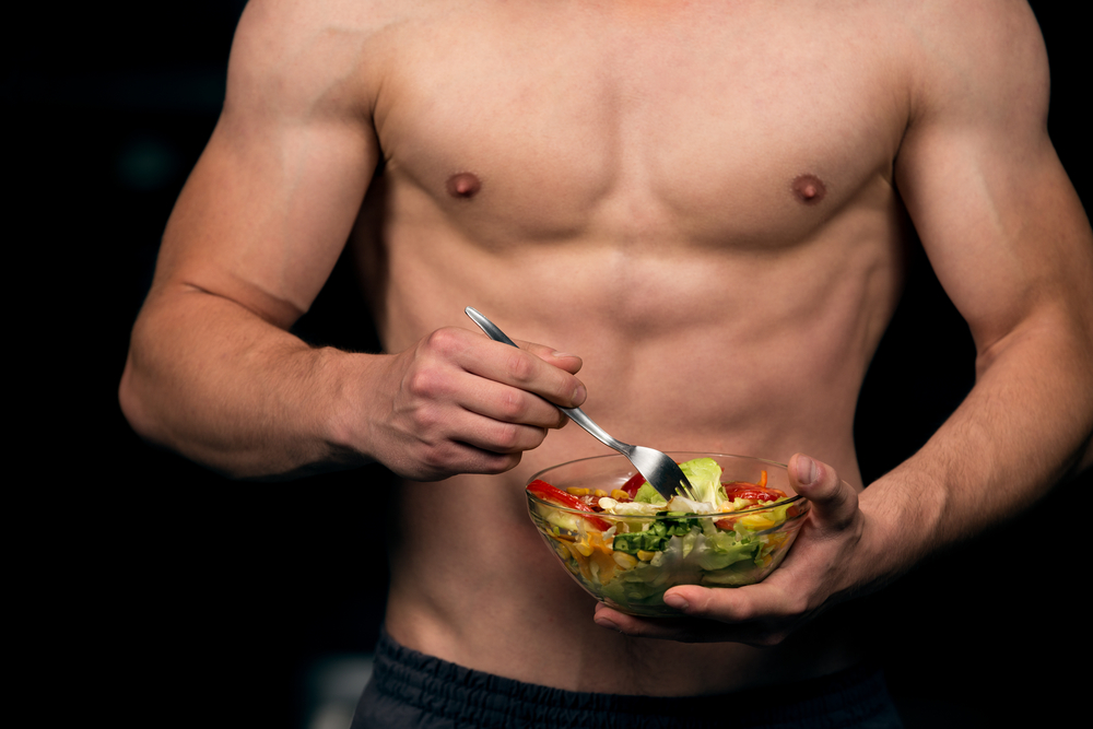 fit man eating fresh salad