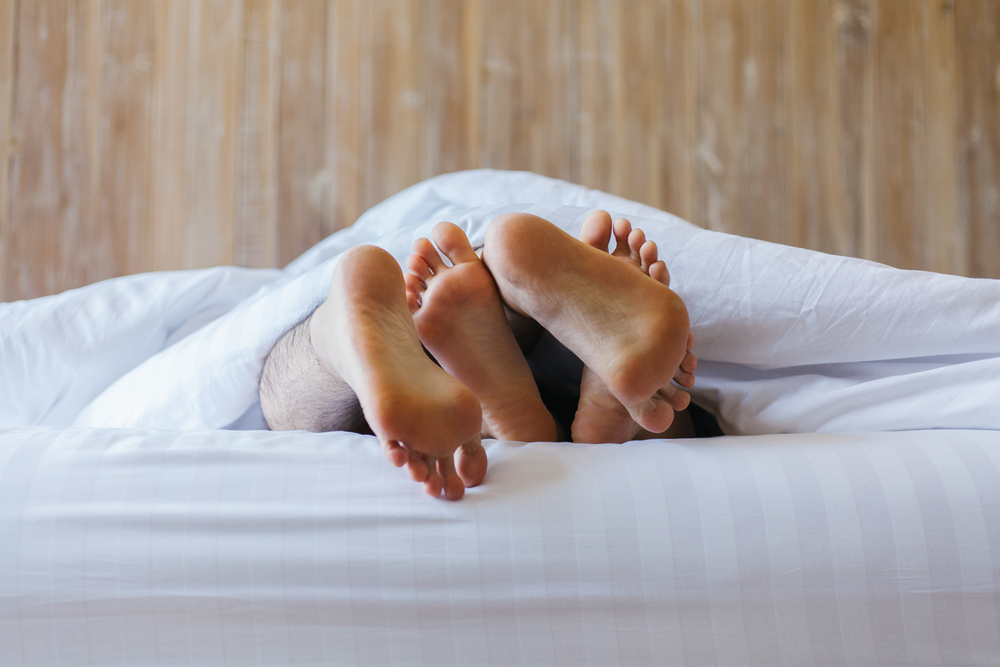 couple's feet, sex under covers