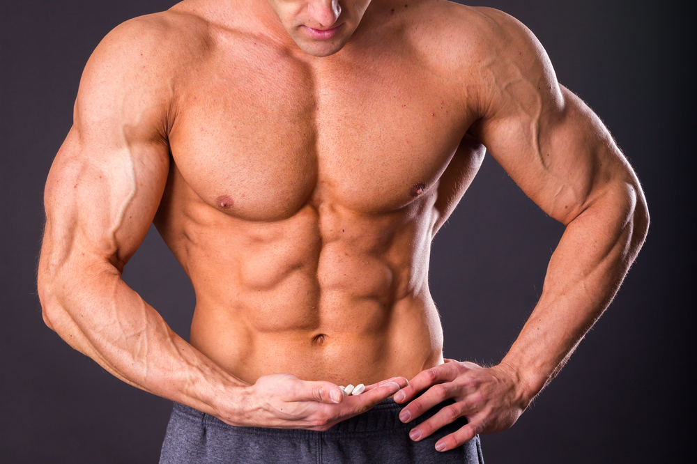 muscular guy holds male enhancement supplements