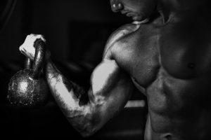 strong muscular man lifts kettle bell