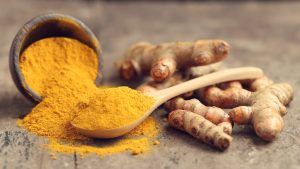 turmeric roots and powder in spoon