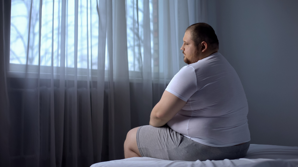 depressed obese man in bed