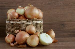 raw white onions in a basket