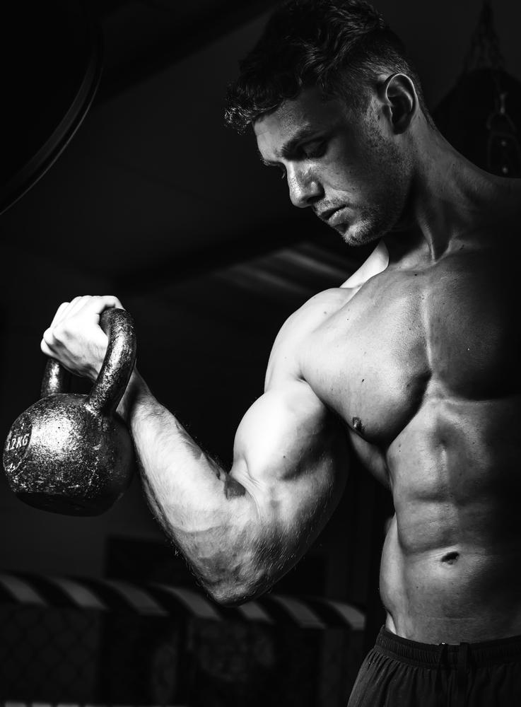 muscular man lifting kettle bell