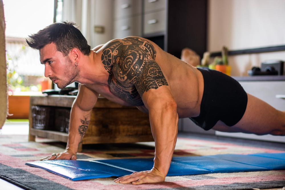 tattooed buff guy doing push ups at home