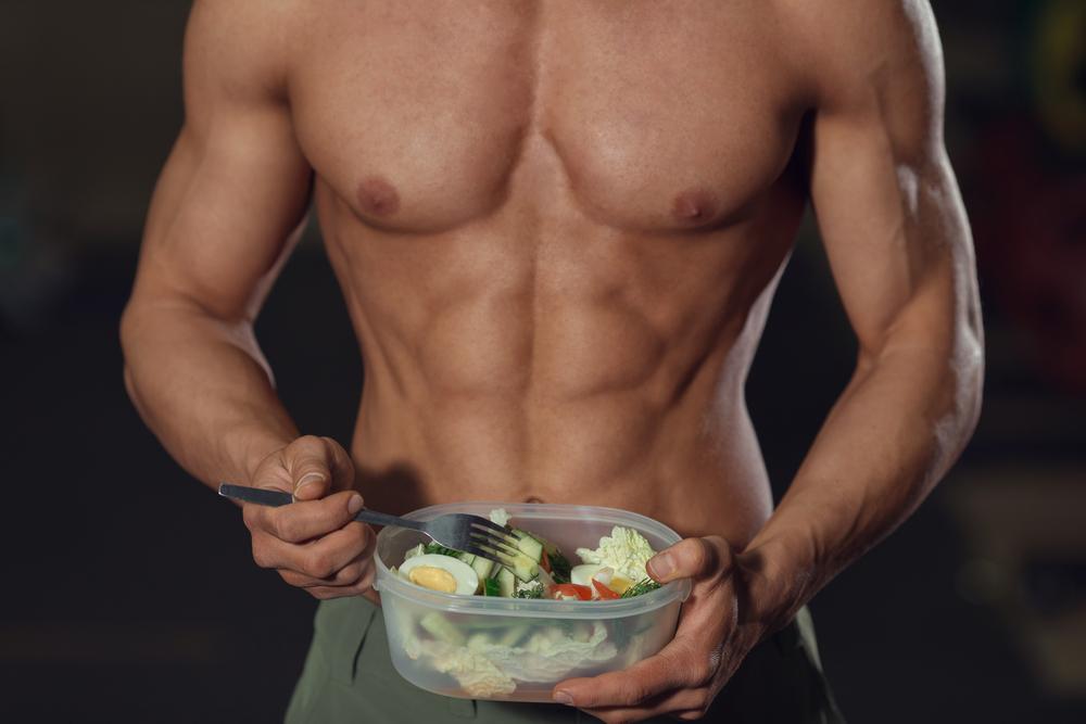 muscular guy eating salad