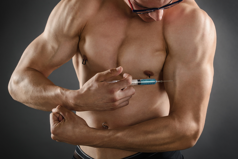 muscular guy injecting his arm