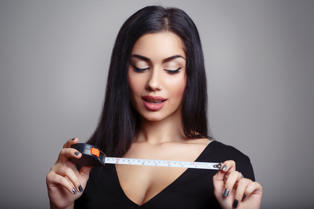 woman holding up tape measure on penis size