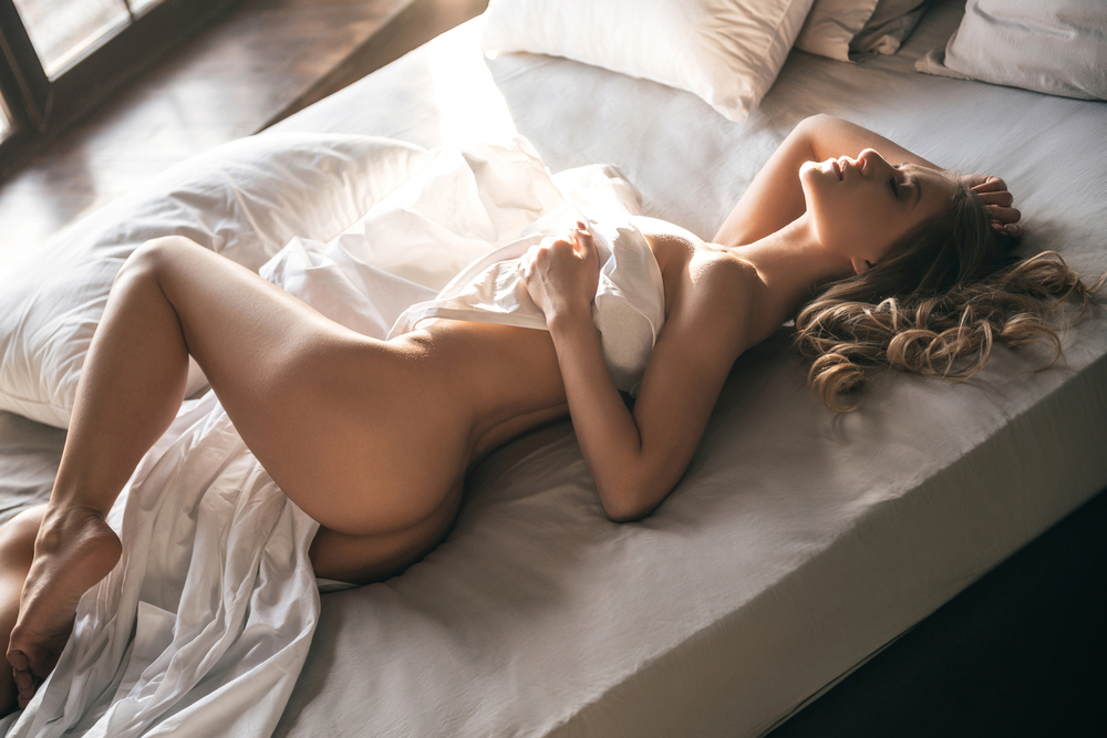 naked woman in bed in sensual pose
