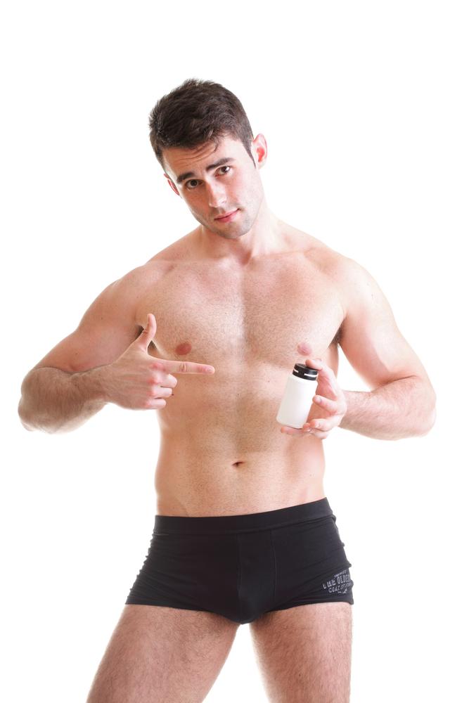 man in underwear with male enhancement supplement bottle
