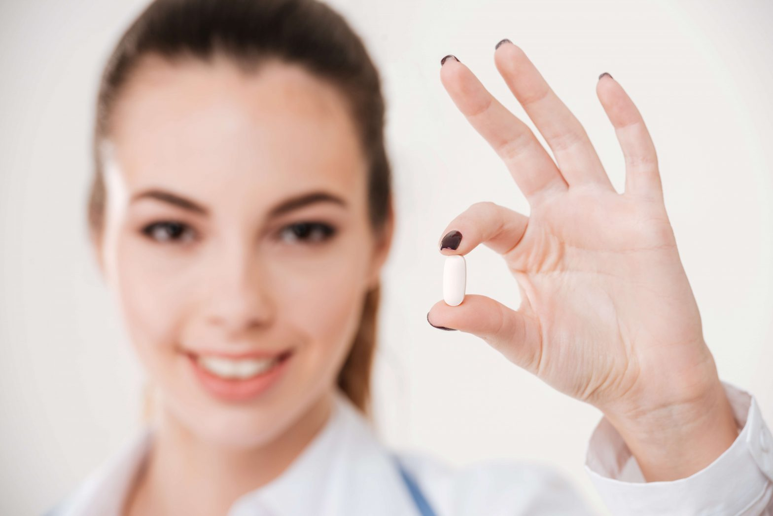 female doctor holding out a capsule