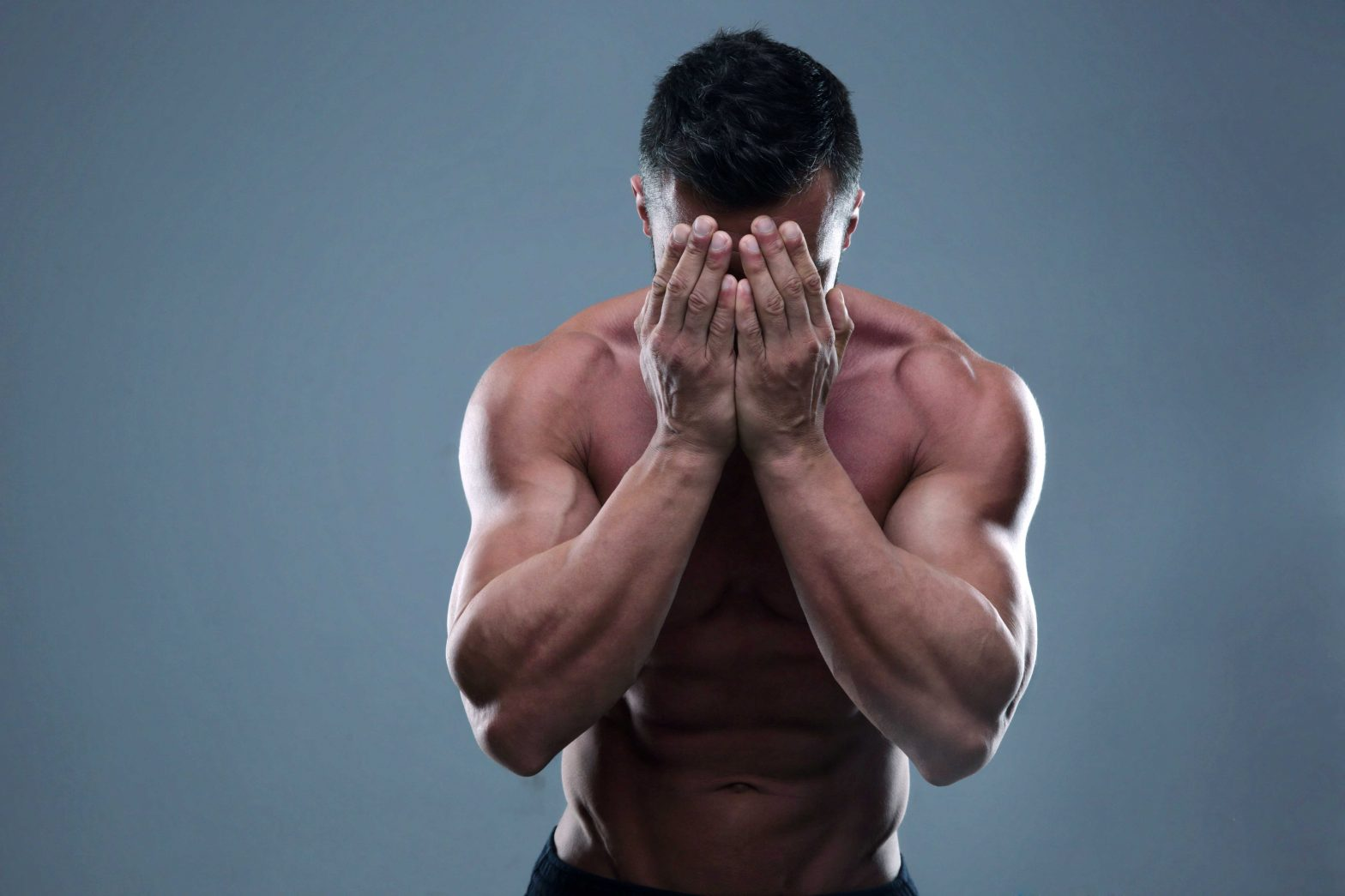 ripped guy burying face in hands