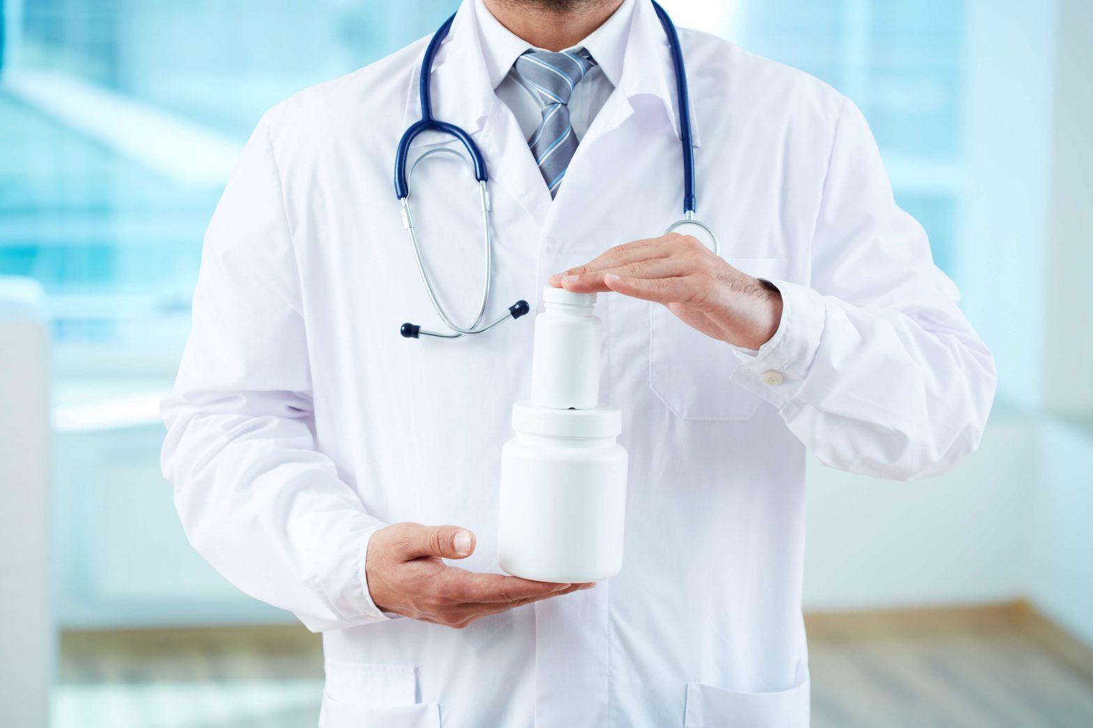doctor holding pill bottles