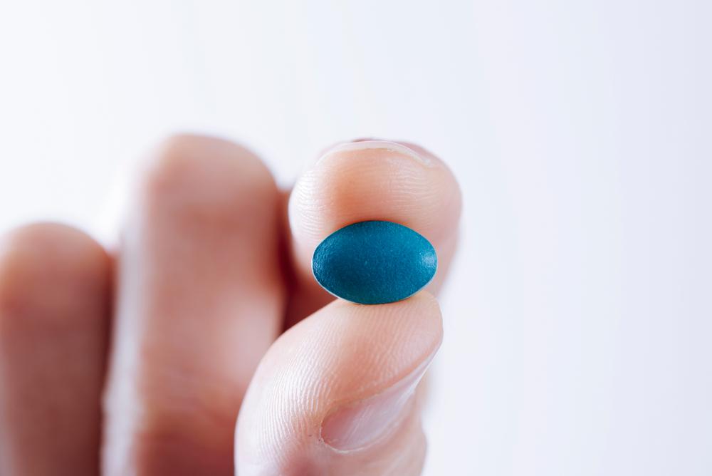 holding blue viagra pill