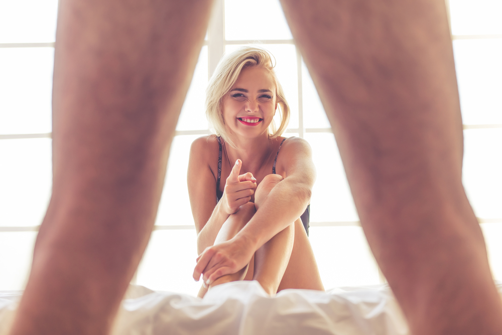 woman happy with what she sees in bed