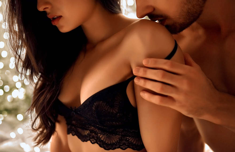 man kissing woman on shoulder