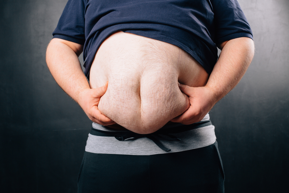 obese man holding belly fat