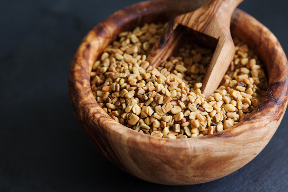 fenugreek seeds in wooden bowl