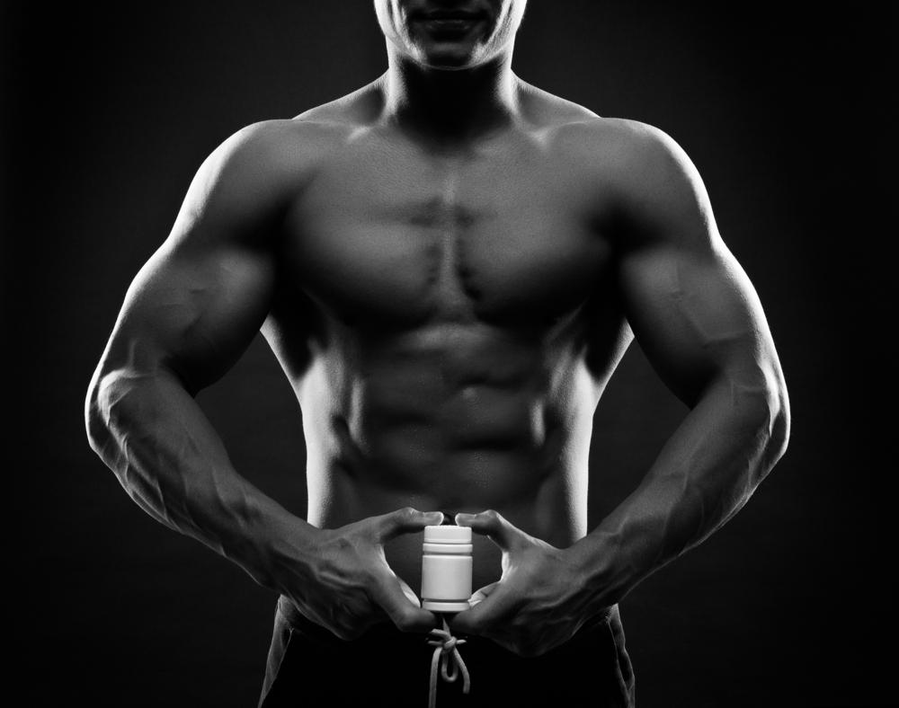 fit guy holding male enhancement pill supplement bottle