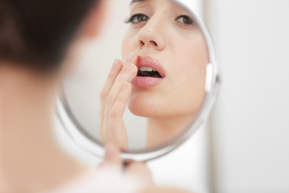 checking cold sore in the mirror