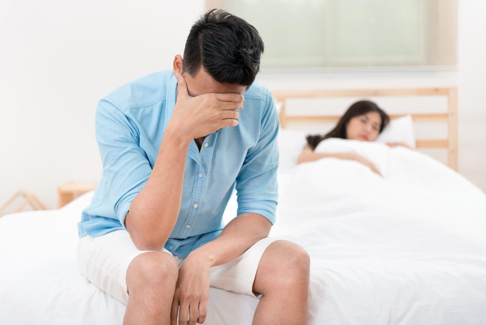 depressed man on edge of bed
