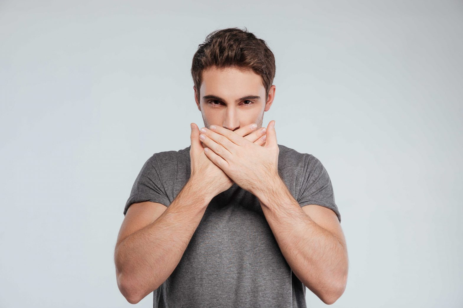 man covers mouth with both hands