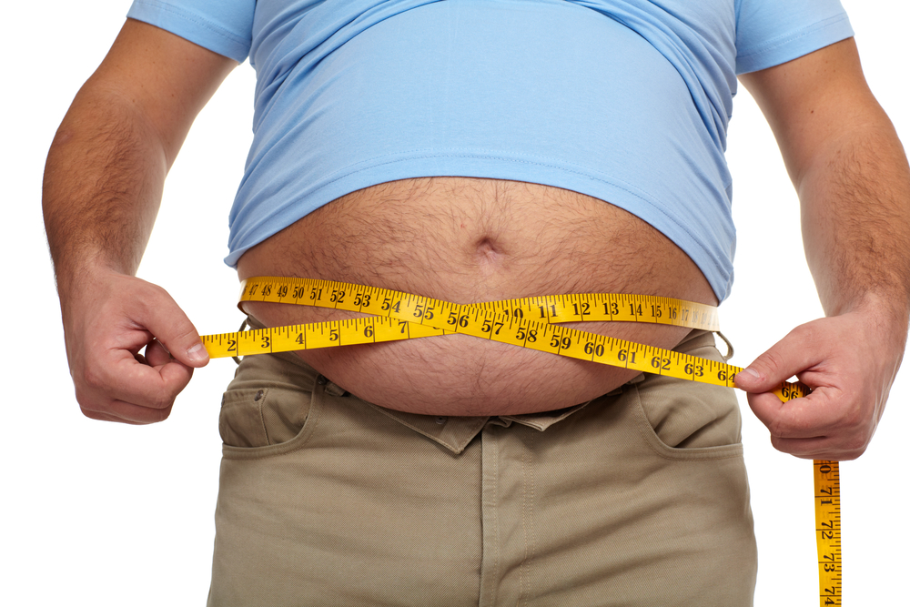 obese man measures waist
