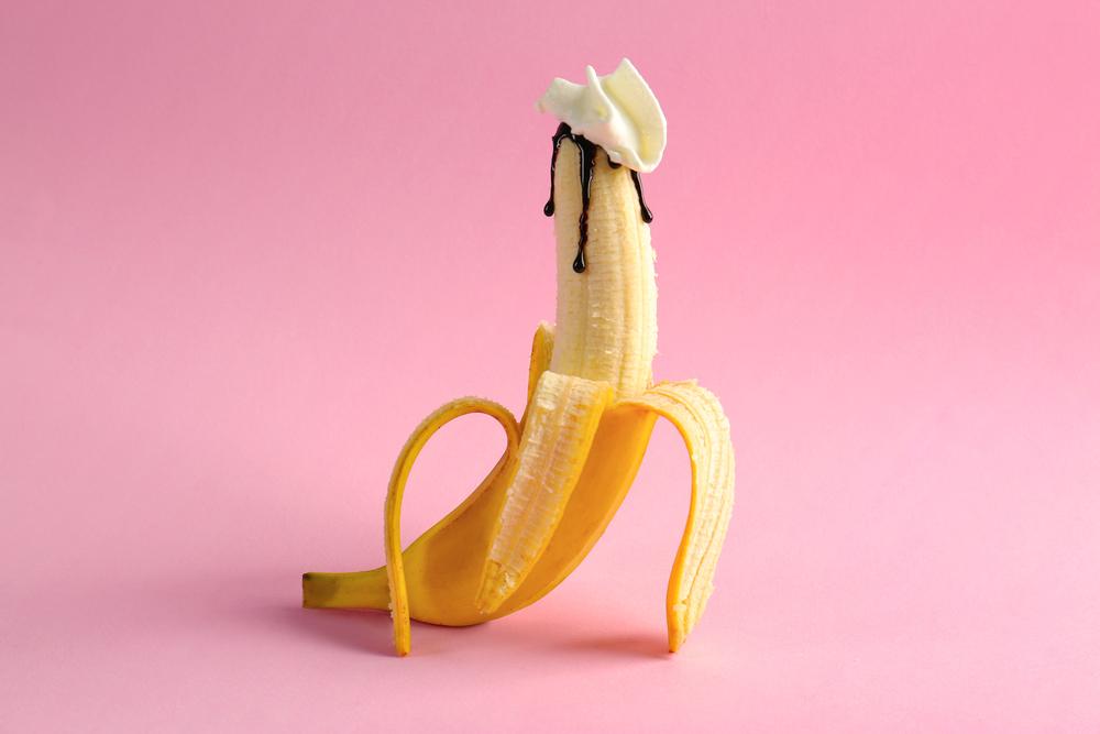 half peeled banana with cream and syrup