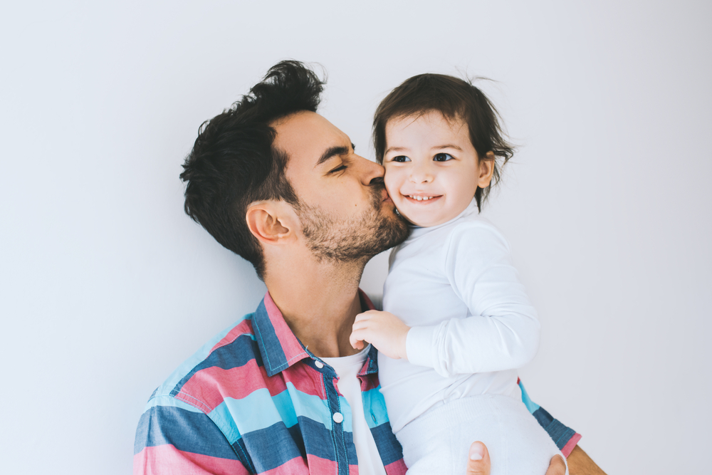 dad kissing his young daughter