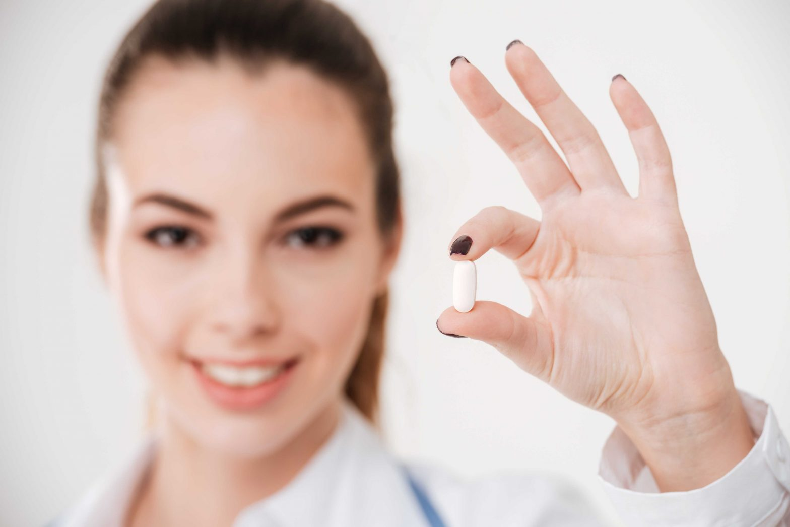 female doctor holding up a pill