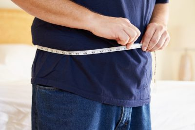 overweight man measuring belly