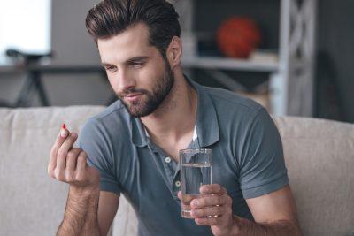 man inspecting medication