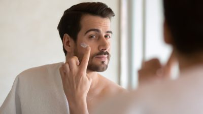 man putting on a moisturizer